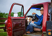 Cowboy peers of truck with his dog.<br />