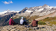 Hikers on Sahale Arm admire El Dorado Peak (left) and Forbidden Peak (far right) in North Cascades National Park, Washington, USA. Panorama stitched from 2 images.