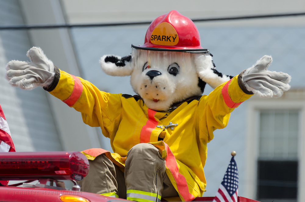 BAR HARBOR, MAINE, July 4, 2014. Sparky the Fire Dog waves from the top of a fire truck in the Independence Day parade.