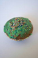 homemade cup cake iced with green icing and covered in hundreds and thousands dots for St Patricks Day