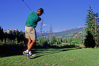 A male golfer tees off at the 16th hole on the Whistler Golf Course in Whistler, BC Canada.