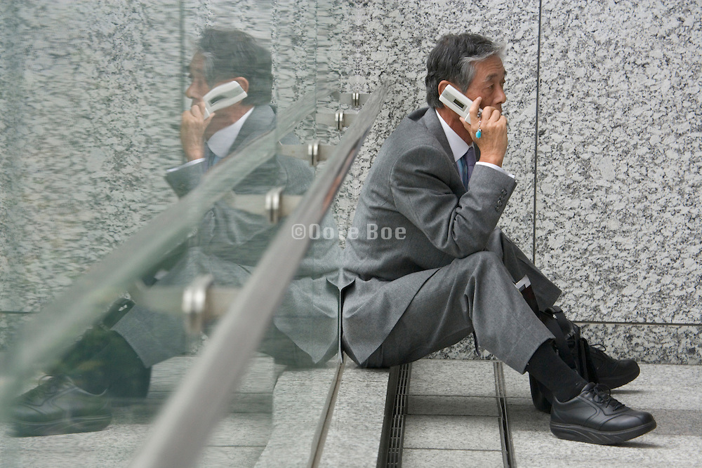 Japanese businessman sitting while talking on his cellphone
