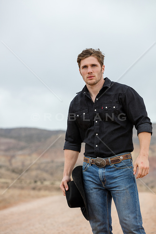 rugged All American cowboy outdoors holding his cowboy hat