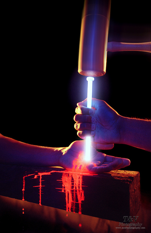 A glowing nail being driven into a bleeding hand with a wood mallet.Black light