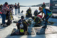 Tim McDonald lowers Jane Sellers into Meredith Bay during the ice dive training and demo Saturday afternoon with East Coast and Central NH Divers.  (Karen Bobotas/for the Laconia Daily Sun)
