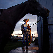 Denny Amos readies his horse before riding in the bi-annual cattle roundup at the Bar B ranch near Albia, Iowa.  Calves were roped and seperated from the herd for vaccinations, branding and the placement of growth stimulant implants.  The male cows were also castrated.  Owner Catherine Bay runs the operation with a herd of over 2,000 cattle.