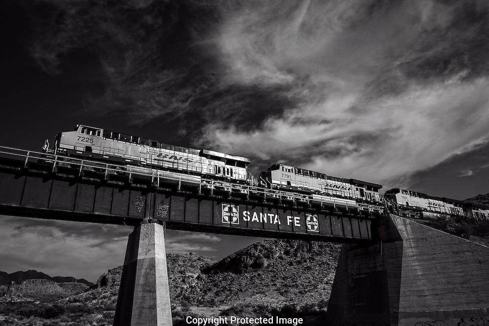 Monochrome photograph of Burlington Northern Santa Fe train as it travels east across northern Arizona