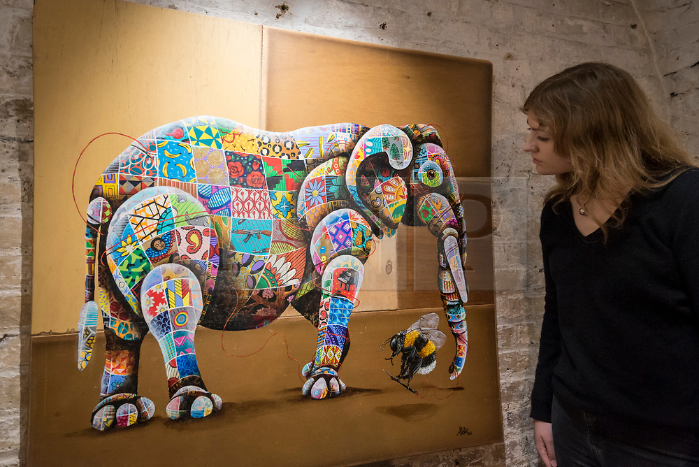 """© Licensed to London News Pictures. 24/05/2018. LONDON, UK. London, UK.  24 May 2018. An assistant views a painting of an African elephant at the preview of """"Missing"""" an exhibition by artist and environmentalist Louis Masai at the Crypt Gallery in Euston.  The exhibition features sculptures, installations and paintings depicting 20 endangered species across the world from the South African penguin to the humble bumble bee.  The show runs 25 to 27 May 2018. Photo credit: Stephen Chung/LNP"""