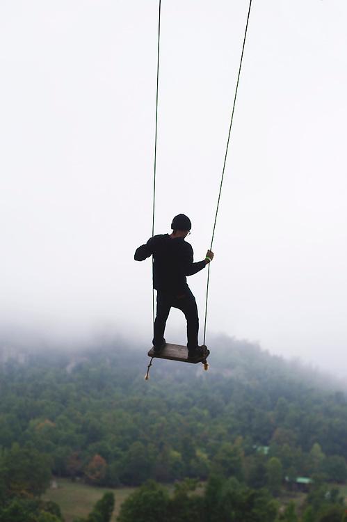 Male on swing in woods