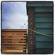 2016 SEPTEMBER 25 - A building and fence with lightbulb string in Georgetown, Seattle, WA. Taken with Instagram App on Apple iPhone. By Richard Walker