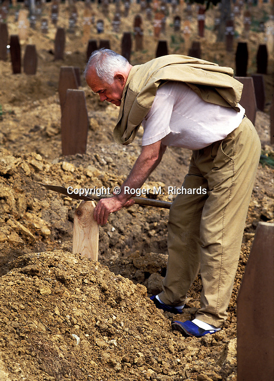 A grave digger taps a marker into a fresh grave at Lion Cemetery during the Bosnian Serb siege of Sarajevo, Bosnia and Herzegovina, September 1992. Almost 2,000 children, and over 10,000 people in total were killed in Sarajevo during the 3-1/2 year siege. (Photo by Roger Richards)