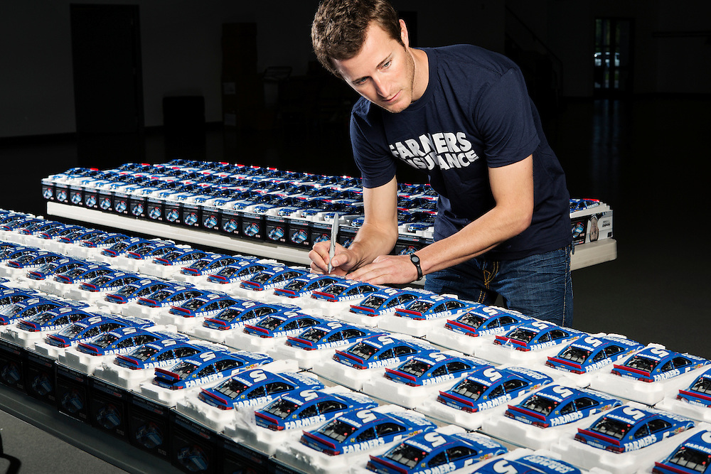 NASCAR Driver Kasey Kahne signs 150 diecast models of his #5 Farmer's Insurance car at the Hendrick Motorsports team center in Concord, N.C., Mon. April 22, 2013. <br /> <br /> Photo by D.L. Anderson for ESPN: The Magazine