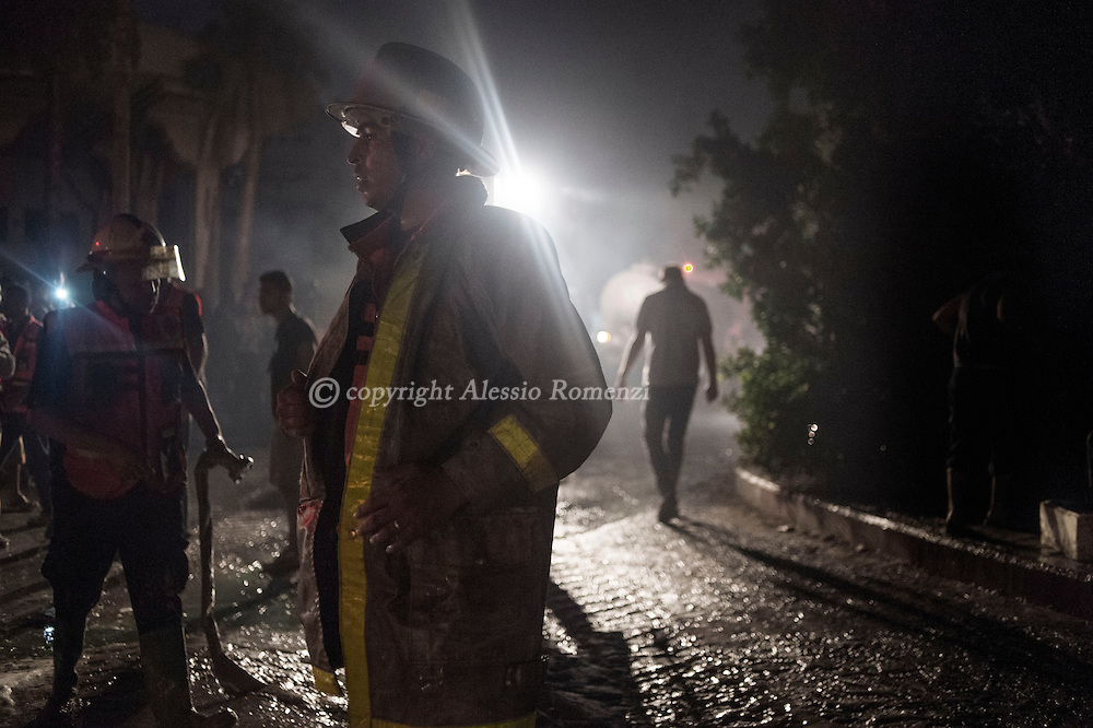 Gaza Strip, Gaza City: Firefighters take a break during their attempt to extinguish the fire at a soap factory in Gaza City after was hit by an Israeli airstrike on August 10, 2012. ALESSIO ROMENZI