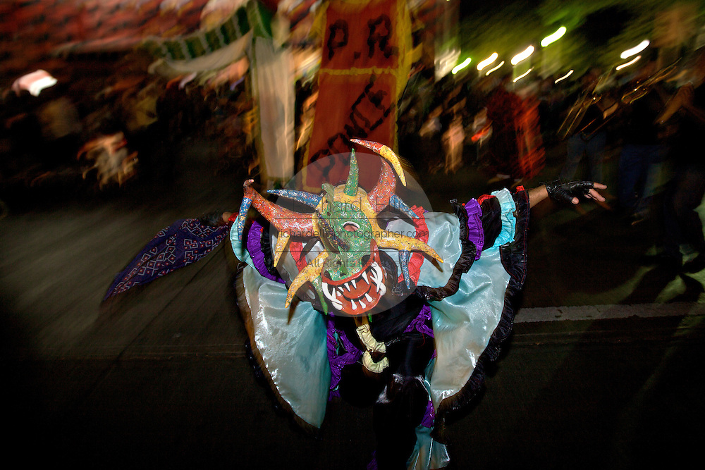 A costumed reveler called a vejigante dances in the streets by the Parque de Bombas during the Carnaval de Ponce February 20, 2009 in Ponce, Puerto Rico. Vejigantes are a folkloric character representing the devil.