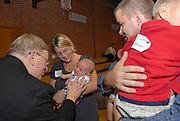 Green Bay Bishop David L. Ricken greets Brian and Tina Haanen's newborn son Sam during a regional gathering Sept. 10 at St. Bernard Church in Green Bay. Six regional gatherings, which include Mass and a reception, are being held in September to give Green Bay Catholcis an opportunity to meet their new bishop. The Haanens, members of St. Philip Church, attended the regional gathering with their five children. (Sam Lucero photo)