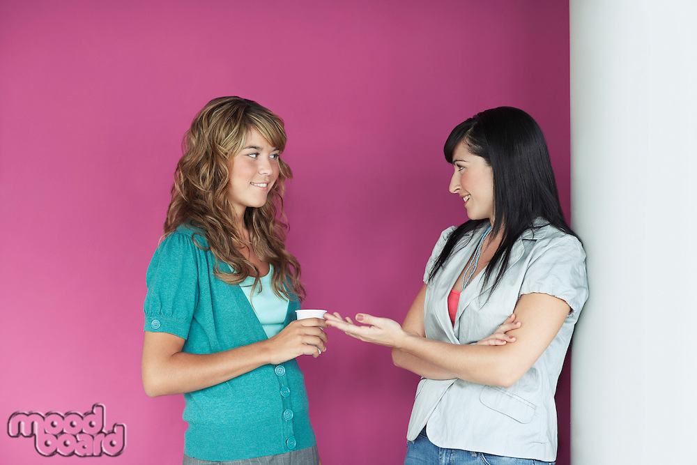 Two young women talking by purple wall