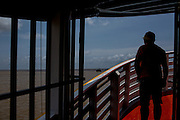 One of the staff of river cruise boat named Breno checks out the ship movement ahead framed by iron grilles as it departs from Bailie archipelago to Macapa, Brazil, Sunday, Oct. 23, 2016. Bathed by the Amazon river mouth  this northernmost capital of 400.000 residents is as filled with canals, informal docks and unregistered boats as it lacks infrastructure and control means for fighting the rising river piracy plaguing passengers and transportation companies. (Dado Galdieri for The New York Times)