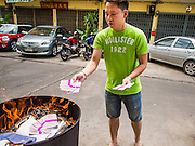 "10 AUGUST 2014 - BANGKOK, THAILAND: A man steps back after dropping a pile of ""Hell Money"" into a burn barrel in Bangkok for Ghost Month. Hell money is a form of joss paper printed to resemble legal tender bank notes and is used in religious ceremonies in Chinese communities. The seventh month of the Chinese Lunar calendar is called ""Ghost Month"" during which ghosts and spirits, including those of the deceased ancestors, come out from the lower realm. It is common for Chinese people to make merit during the month by burning ""hell money"" and presenting food to the ghosts.    PHOTO BY JACK KURTZ"