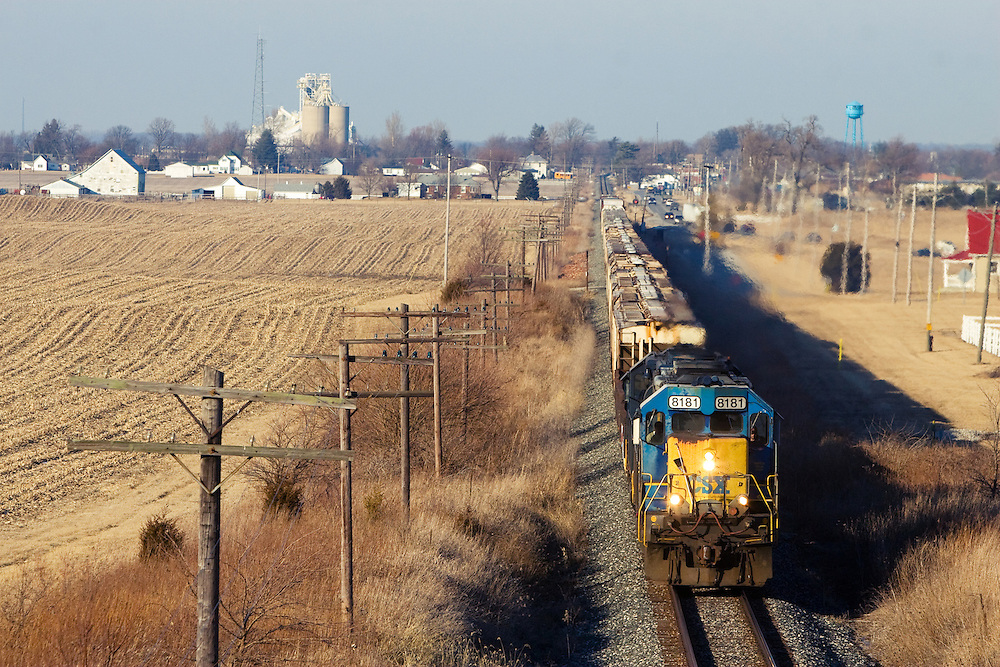 About to pass under Highway 231, a CSX freight train has just passed through Linden, a small town in west central Indiana, seen on the horizon over the flat prairie landscape.