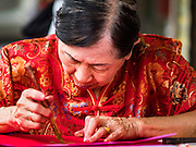 "18 JANUARY 2017 - BANGKOK, THAILAND: A traditional Chinese calligrapher draws New Years greetings that she sells in Bangkok's Chinatown district, before the celebration of the Lunar New Year. Chinese New Year, also called Lunar New Year or Tet (in Vietnamese communities) starts Saturday, 28 January. The coming year will be the ""Year of the Rooster."" Thailand has the largest overseas Chinese population in the world; about 14 percent of Thais are of Chinese ancestry and some Chinese holidays, especially Chinese New Year, are widely celebrated in Thailand.      PHOTO BY JACK KURTZ"