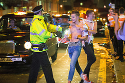 "© Licensed to London News Pictures . 16/11/2015 . Manchester , UK . Police push people back from the path of oncoming taxis . Annual student pub crawl "" Carnage "" at Manchester's Deansgate Locks nightclubs venue . The event sees students visit several clubs over the course of an evening . This year's theme is "" Animal Instinct - unleash your beast "" . Photo credit : Joel Goodman/LNP"