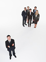 Businessman standing apart from group