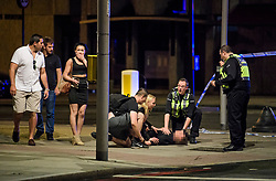 © Licensed to London News Pictures. 03/06/2017. London, UK. A man on the floor being treated on Southwark Street, near London Bridge following a terrorist attack involving a vehicle and pedestrians. A white transit van deliberately ran down people crossing the bridge and three men jumped out attacking people with knives. Photo credit: Ben Cawthra/LNP