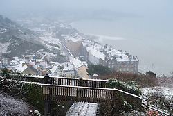 © Licensed to London News Pictures. 10/12/2017. Aberystwyth, UK. The first snow of the winter at Aberystwyth on the Welsh coast, as the wintry conditions spread of much of the middle of the UK.  People are out  walking on Constitution Hill overlooking the town, making the most of the snowy scenes .Photo credit: Keith Morris/LNP
