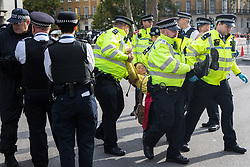 London, UK. 9 October, 2019. Police officers arrest a climate activist from Extinction Rebellion who had blocked Whitehall on the third day of International Rebellion protests to demand a government declaration of a climate and ecological emergency, a commitment to halting biodiversity loss and net zero carbon emissions by 2025 and for the government to create and be led by the decisions of a Citizens' Assembly on climate and ecological justice.