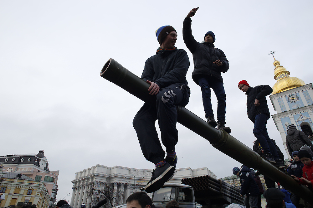 People play and take selfies atop a T-64 tank on display in Mykhailivska Square on February 22, 2015 in Kyiv, Ukraine. The weapons system was one of several items that the Ukrainian government displayed this weekend as evidence of Russian involvement with separatists in the eastern Donbas region.