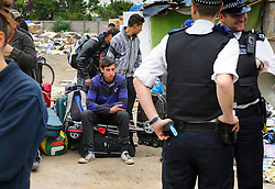 © Licensed to London News Pictures. 26/06/2013 London, UK. Romanian immigrants wait to be served eviction papers after a dawn raid on Hendon Football Club, Hendon North West London. The 68 illegal immigrants were removed in a joint Home Office Immigration, Met Police and homeless charity operation after the site has been occupied for more than 2 years.<br /> Photo credit : Simon Jacobs/LNP