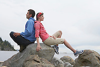 Couple sitting back to back on rocks by ocean