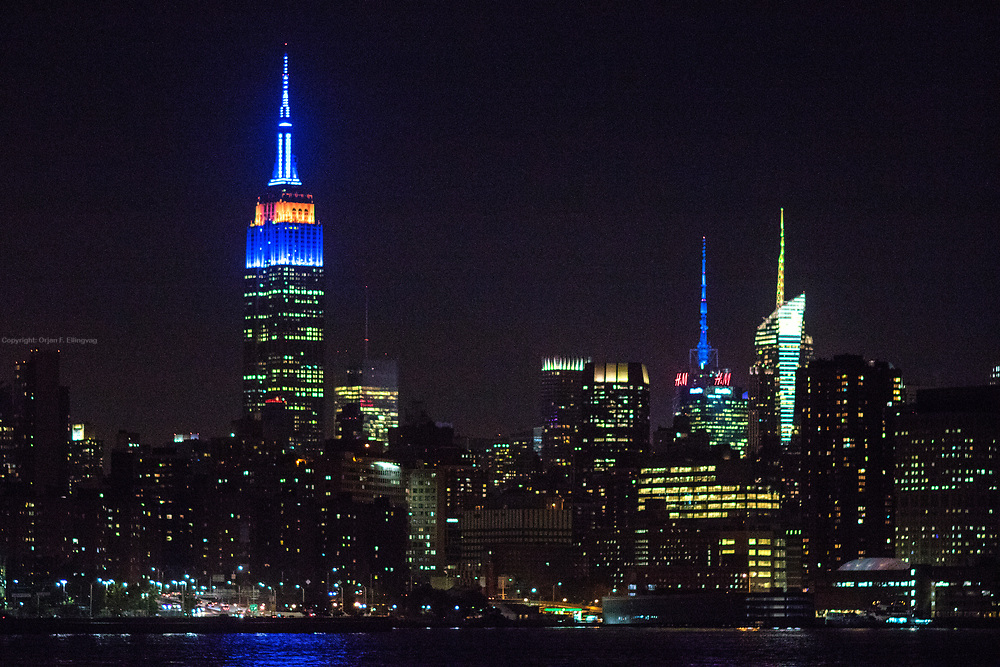 Nighttime Manhattan Skyline, with the Empire State Building, ESB, illuminated in blue and orange to honor the New York Islanders.