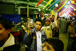 """In the Moqattam area of greater Cairo, Egyptians hold an engagement party for someone from the community. This particular community are referred to as the """"Zabaleen,"""" or trash collectors. Mostly Coptic Christians, the Zabaleen are responsible for collecting and recycling most of Cairo's waste. Weddings, engagement parties, and other events are celebrated in the neighborhood streets. Food, alcohol and hashish were served to people who came to celebrate the occasion while music played and three belly dancers performed for the all-male crowd.///Boys take pictures of the belly dancers with their mobile phones."""