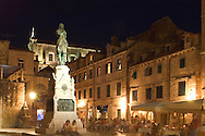 People eating at an outdoor restaurant at night in Gundulic's Square  Dubrovnik, Croatia<br /> c. Ellen Rooney