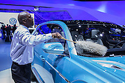 New York, NY - 1 April 2015. A man dusts a new VW Cross Coupé at the New York International Auto Show. The car is a hybrid vehicle, and was introduced at the Detroit Auto Show in January, 2015.
