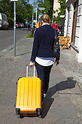 Germany, Berlin female tourist  pulls her luggage