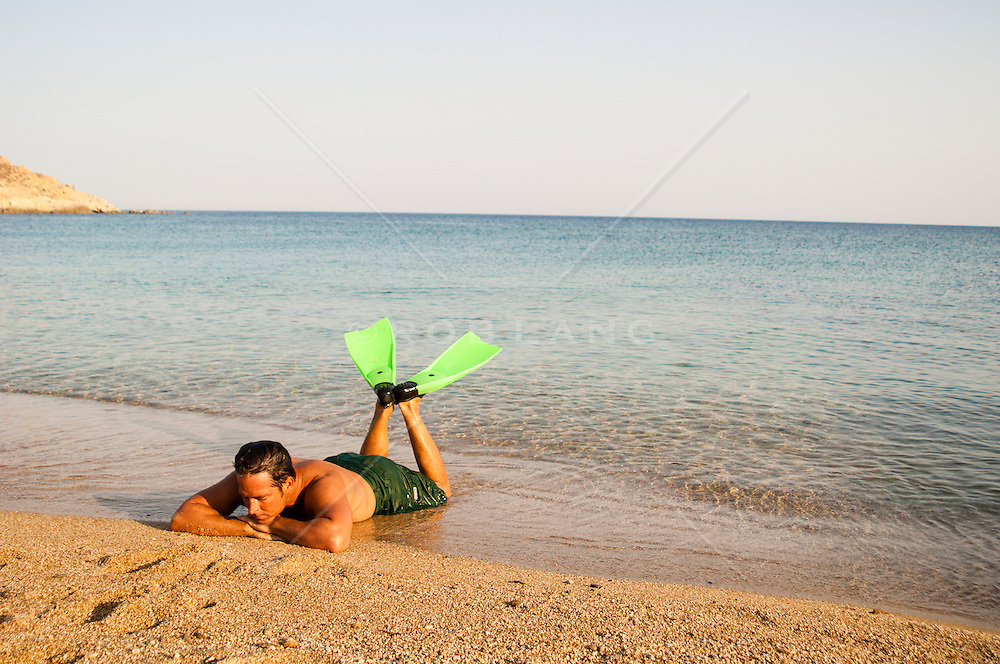 man with diving fins relaxing by the shore in Greece