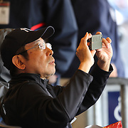 A fan takes pictures of Masahiro Tanaka, New York Yankees, pitching during the New York Yankees V Tampa Bay Rays, Major League Baseball game at Yankee Stadium, The Bronx, New York. 3rd May 2014. Photo Tim Clayton