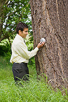 A mixed ethnicity businessman adjusting a thermostat on a tree outside.
