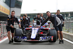 A Red Bull F1 car is brought into the paddocks by mechanics during Paddock Day of the 2017 British Grand Prix at Silverstone Circuit, Towcester.