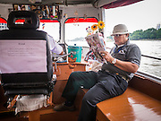 09 OCTOBER 2012 - BANGKOK, THAILAND:  A man reads his daily newspaper on a Chao Phraya Express boat in Bangkok, Thailand. Boats and ships play an important in daily life in Bangkok. Thousands of people commute to work daily on the Chao Phraya Express Boats and fast boats that ply Khlong Saen Saeb. Boats are used to haul commodities through the city to deep water ports for export.     PHOTO BY JACK KURTZ