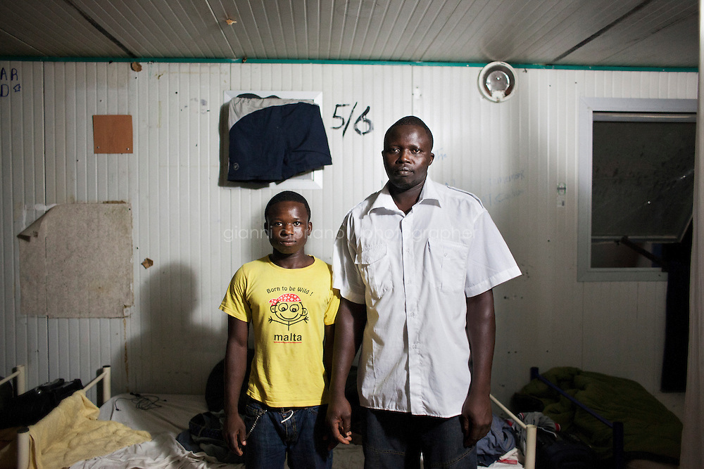 Hal Far, Malta - 20 August, 2012:  Two Ghanaian brothers stand in the container they live in and that they share with other 8 Sub-Saharan migrants in the Hal Far Hangar Site in Hal Far, Malta, on 20 August, 2012.<br /> <br /> The Hangar Open Center is a field with an ex-aircraft hangar which, until 2011, included Swiss Red Cross tents in a dark, non lit space in very poor conditions and with inflamable oil on the floor. Today, the hangar is closed and the migrants live in 34 external containers with no water. <br /> <br /> The Open Centres in Malta serve as a temporary accomodation facility, but they ended becoming permanent accomodation centres, except for those immigrants who receive subsidiary protection or refugee status and that are sent to countries such as the United States, Germany, Poland, and others. All immigrants who enter in Malta illegally are detained. Upon arrival to Malta, irregular migrants and asylum seekers are sent to one of three dedicated immigration detention facilities. Once apprehended by the authorities, immigrants remain in detention even after they apply for refugee status. detention lasts as long as it takes for asylum claims to be determined. This usually takes months; asylum seekers often wait five to 10 months for their first interview with the Refugee Commissioner. Asylum seekers may be detained for up to 12 months: at this point, if their claim is still pending, they are released and transferred to an Open Center.<br /> <br /> Gianni Cipriano for The New York Times