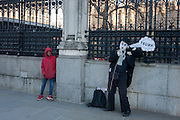 Outside Britain's Palace of Westminster parliament, a young black boy looks sideways at a Charlie Chaplin character making a Donald trump joke, on the day of Trump's inauguration as the 45th US president, on 20th January, in Parliament Square, London borough of Westminster, England.