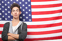 Portrait of young mixed race man with arms crossed standing against American flag