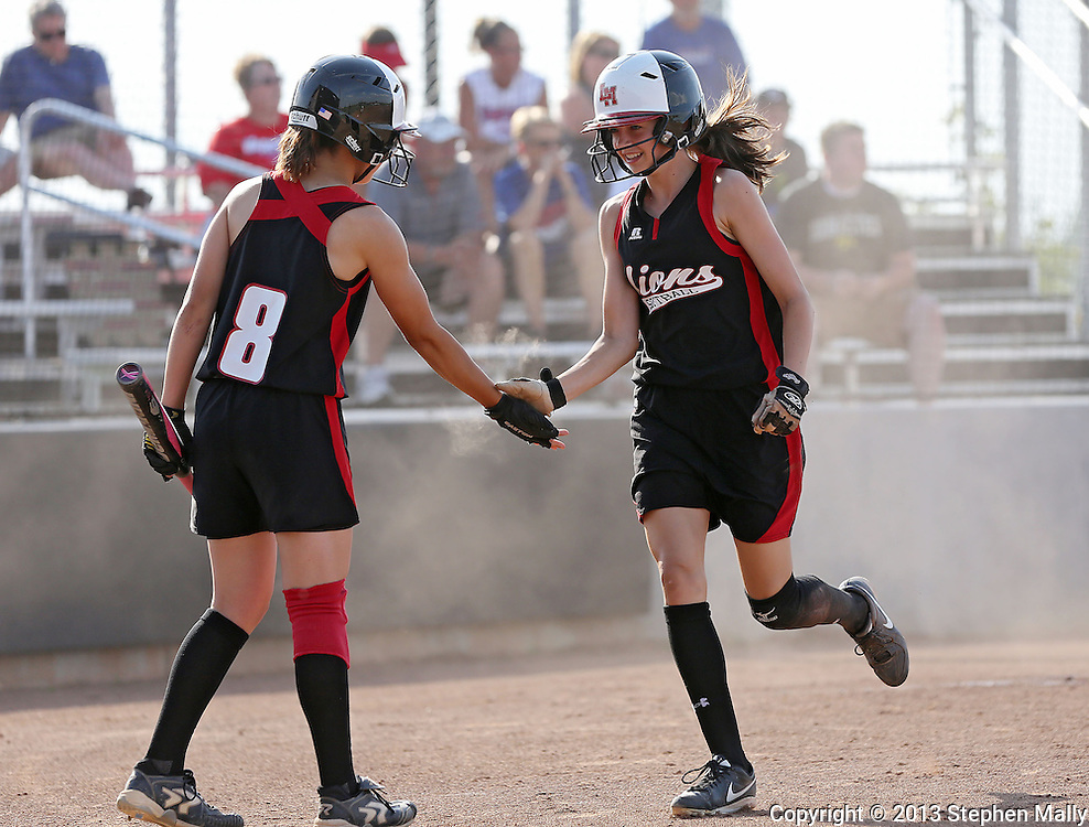 Linn-Mar's Amber Decker (4) is greeted by Elison Ollinger (8) after scoring a run during the softball game between Cedar Rapids Washington and Linn-Mar at Oak Ridge Middle School in Marion on Thursday, June 20, 2013. The Lions defeated the Warriors 7-6 in 9 innings.