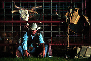 A bull rider mentally prepares for his ride as a bull behind him appears already ready