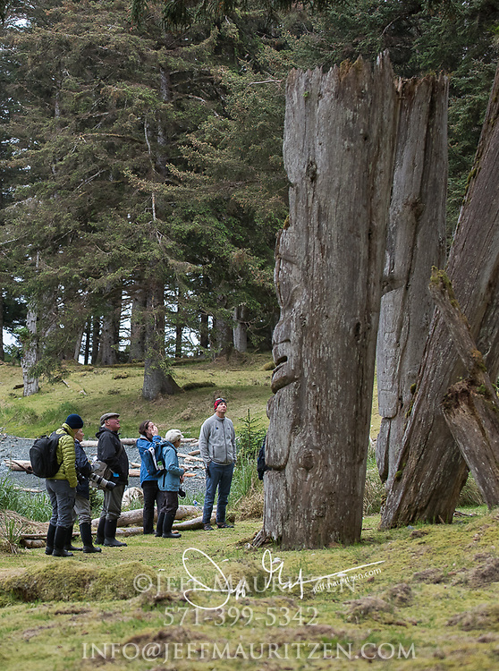 Visitors look up at standing mortuary poles at Ninstints on Sgang Gwaay, a UNESCO World Heritage Site at Gwaii Haanas National Park, British Columbia, Canada.