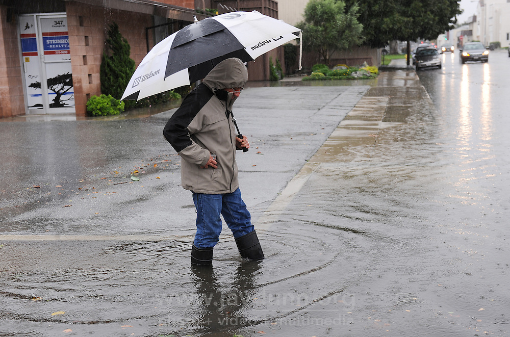 """Standing at the corner of W. San Luis St. and Cayuga St. in Salinas at 2:00 PM, resident Miguel Payan wonders at the volume of rain caused by December 11th's """"Pineapple Express"""" storm."""