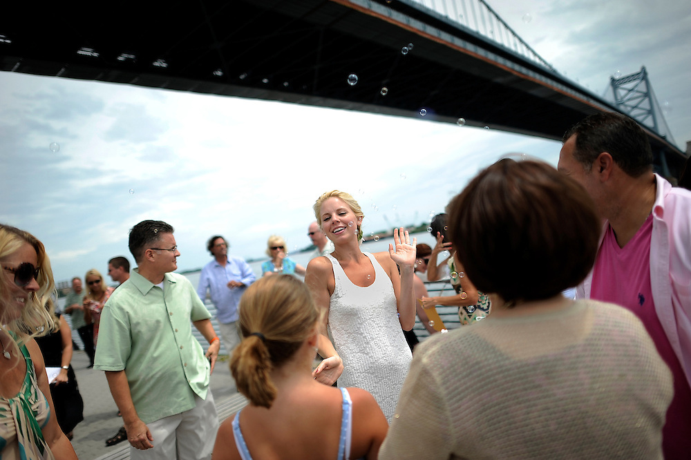 A wedding at Race Street Pier underneath the Benjamin Franklin Bridge in Philadelphia, Pennsylvania.